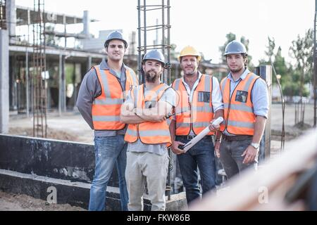 Portrait of site manager and building team on construction site - Stock Photo