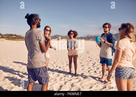 Group of young people standing in circle on the beach and playing with ball. Young friends playing ball game on - Stock Photo
