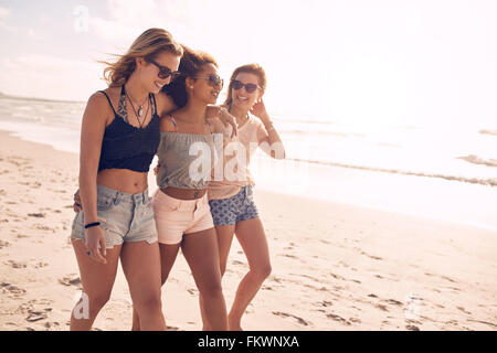 Portrait of three young female friends walking on the sea shore. Multiracial young women strolling along a beach on a summer day