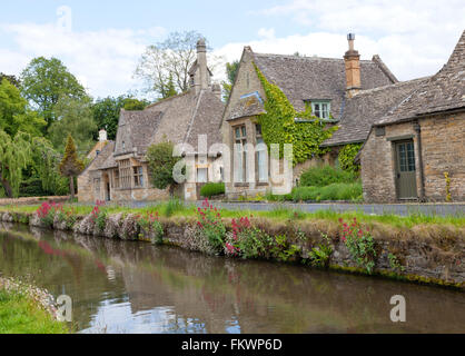 English stone cottages in the traditional Cotswold style along banks of  river  Eye with wild flowers - Stock Photo