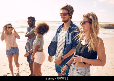 Group of friends walking along a beach at summertime. Happy young people enjoying a day at beach. - Stock Photo