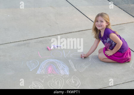 A smiling little girl drawing a design on the sidewalk with chalk. Room at the top for copy text. - Stock Photo