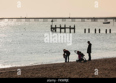 Young Family on Beach at Waters Edge Enjoying Bright Spring Sunshine with Southend Pier in Background - Stock Photo