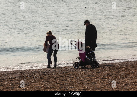 Young Family on Beach at Waters Edge Enjoying Bright Spring Sunshine - Stock Photo