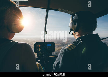 Two pilots in a helicopter while flying on a sunny day. rear view shot of man and woman pilots - Stock Photo