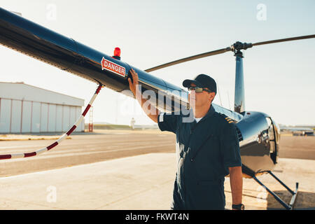 Male pilot standing at the tail of a helicopter and looking away. Mechanic inspecting helicopter before take off. - Stock Photo