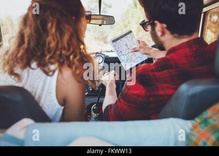 Rear view of a young couple in their car checking a map. Young man and woman on a road trip. - Stock Photo