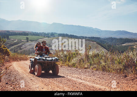 Young man and woman having fun while driving a quad bike. Young couple enjoying off road vehicle ride on a summer - Stock Photo