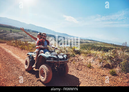 Young couple on an off road adventure. Man driving quad bike with girlfriend sitting behind and enjoying the ride - Stock Photo
