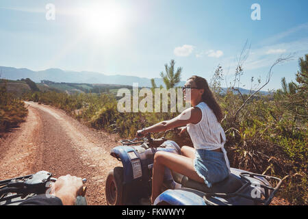 Young woman on quad bike on a trail. Young woman driving all terrain vehicle in nature on a sunny day. - Stock Photo