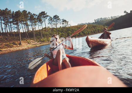 Young people kayaking on a lake. Smiling young woman kayakers with a man paddling kayak in the background. - Stock Photo