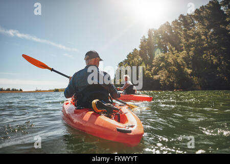Outdoor shot of mature man canoeing in the lake with woman in background. Couple kayaking in the lake on a sunny - Stock Photo