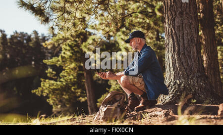 Mature man hiker sitting by a tree in forest and checking his position by using a compass. Senior man on hike in - Stock Photo