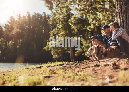 Portrait of senior couple sitting by a lake on a summer day. Mature man and woman using compass for directions. - Stock Photo