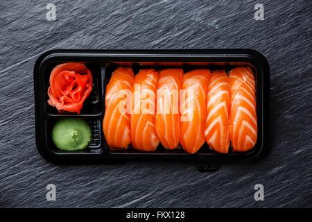 Salmon nigiri sushi in plastic box packaging tray on black stone slate background - Stock Photo