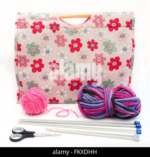 Pink flower patterned knitting / craft bag with knitting needles, pink and multi colour wool and scissors on a white - Stock Photo