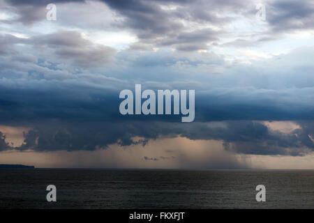 Storm over the ocean in Bali from Tanah lot in early sunset colors - Stock Photo