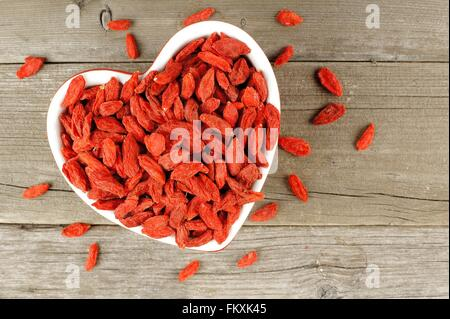Heart shaped bowl filled with dried goji berries over a wood background - Stock Photo