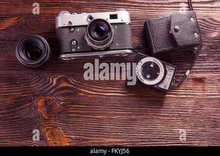Old film camera, lenses and old exposure meter on a wooden background - Stock Photo