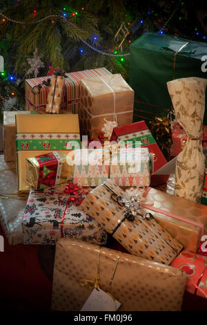 A pile of elegantly wrapped Christmas gifts. Part of a Christmas tree with lights forms the background. - Stock Photo