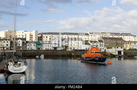 Seafront houses and accommodation overlooking boats in Portrush Harbour at Portrush, County Antrim, Northern Ireland - Stock Photo