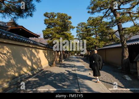 A monk walking down a path between walls in the Daitoku-ji zen buddhist temple in Kyoto - Stock Photo