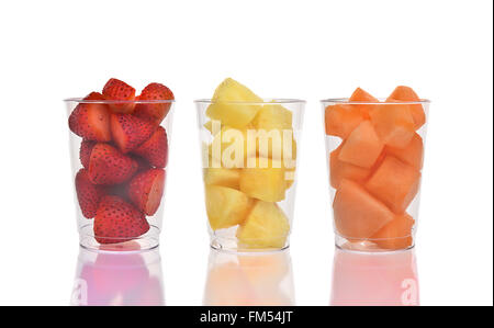 Three fresh fruit cups on white with reflection. Strawberries, Pineapple and Cantaloupe in plastic cups. - Stock Photo