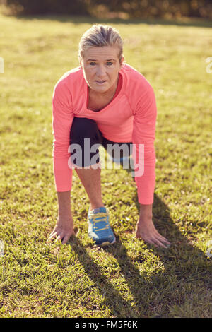 Portrait of aan active senior woman looking up at the camera, while doing a warm up runner's lunge in morning sunlight - Stock Photo
