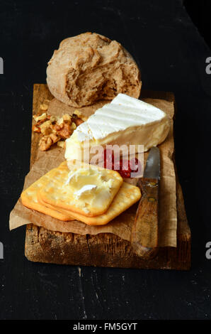 cheese and crackers on old wooden board - Stock Photo