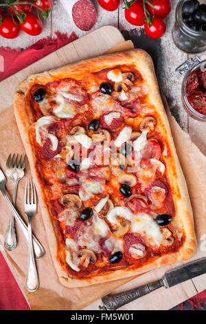 Homemade rectangular pepperoni pizza on a rustic table with ingredients. Photographed from directly above. - Stock Photo