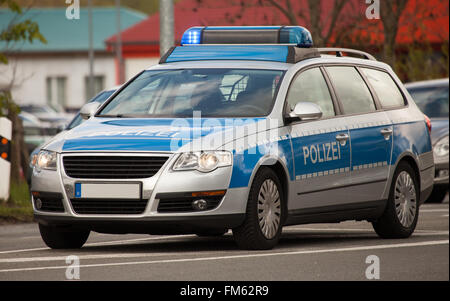 german police patrol car with flashing blue lights on the street - Stock Photo