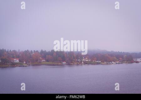 Swedish island in the morning mist, early autumn morning in Scandinavia - Stock Photo