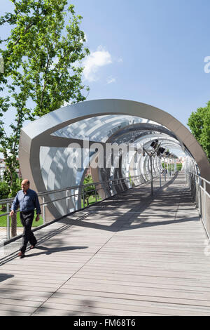 A view of a modern new metal structure in Madrid called The Pasarela del Arganzuela as a male pedestrian crosses - Stock Photo