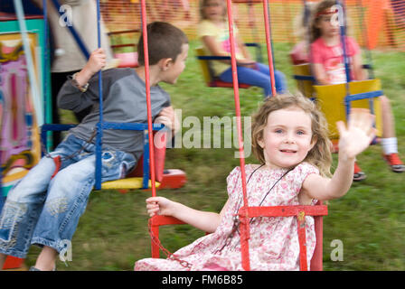 TEWKESBURY, GLOS. UK - July 2013: Little girl waving from the Merry-go-Round on 13 July 2014 at Tewkesbury Medieval - Stock Photo