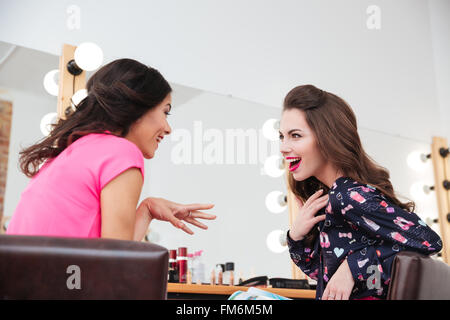Two excited wondered young women talking near the mirror in beauty salon - Stock Photo