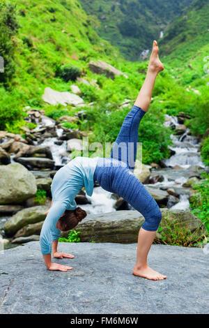 Woman doing yoga asana at waterfall - Stock Photo