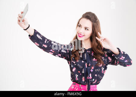 Pretty smiling young woman making selfie using cell phone and showing peace sign over white background - Stock Photo