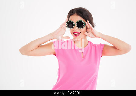 Portrait of happy beautiful young woman in pink top and round sunglasses over white vackground - Stock Photo