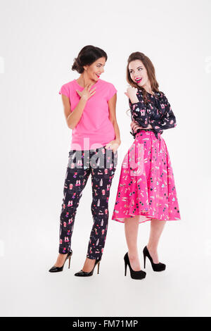 Two happy pretty young women standing and smiling over white background - Stock Photo