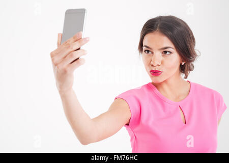 Cute lovely young woman making duck face and taking selfie using smartphone over white background - Stock Photo
