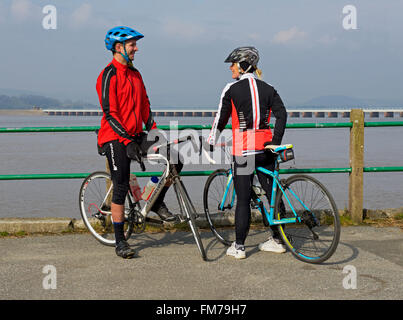 Two cyclists on the promenade at Arnside, Cumbria, England UK - Stock Photo