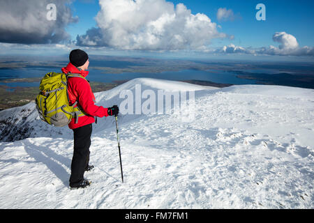 Winter walker looking over Lough Conn from the summit of Nephin mountain, County Mayo, Ireland. - Stock Photo