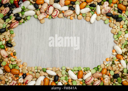Mixed dried legumes and cereals arranged around grey wooden background. Copy space in middle - Stock Photo