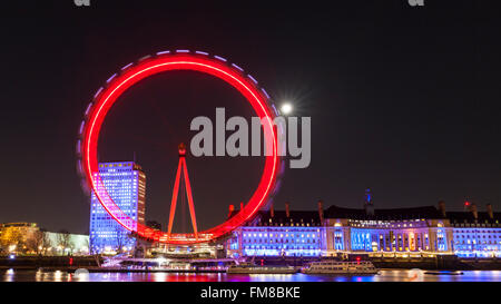 London at night - Illuminated London Eye ferris wheel and city skyline at night, full moon shining behind - Stock Photo