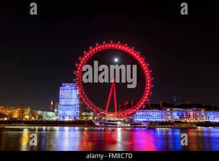 London at night - Illuminated London Eye ferris wheel and city skyline at night, full moon shining behind - Stock Photo