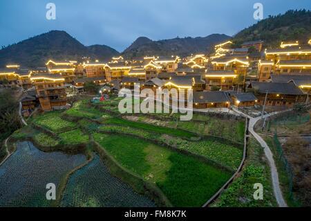 China, Guizhou, Kaili, old village illuminated within the rice paddies - Stock Photo