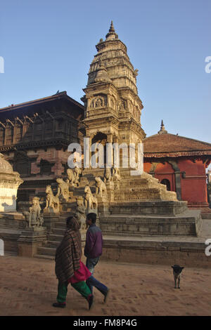 People passing Siddhi Lakshmi Temple, Durbar Square, Bhaktapur, Nepal - Stock Photo