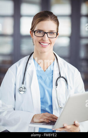 Portrait of smiling female doctor working on laptop - Stock Photo