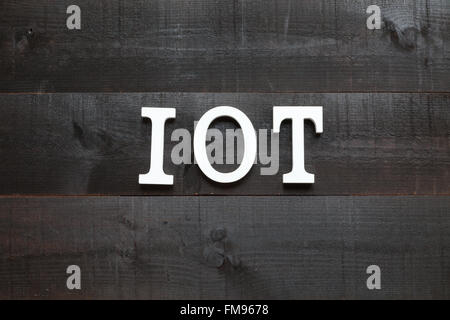 The acronym IOT Internet of things on dark background - Stock Photo