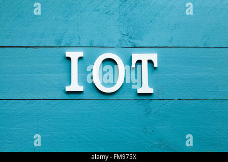 The acronym IOT Internet of things on blue background - Stock Photo